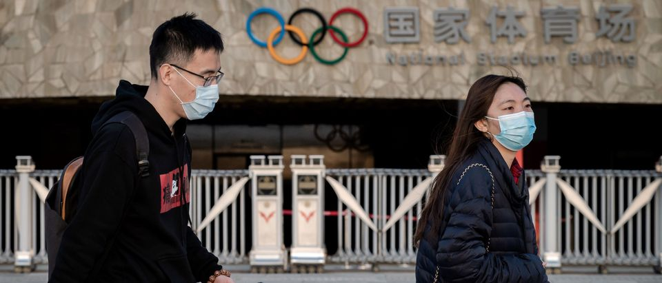 People wearing facemasks as a preventive measure against the COVID-19 novel coronavirus walk at the Olympic park in Beijing on March 23, 2020. (NICOLAS ASFOURI/AFP via Getty Images)