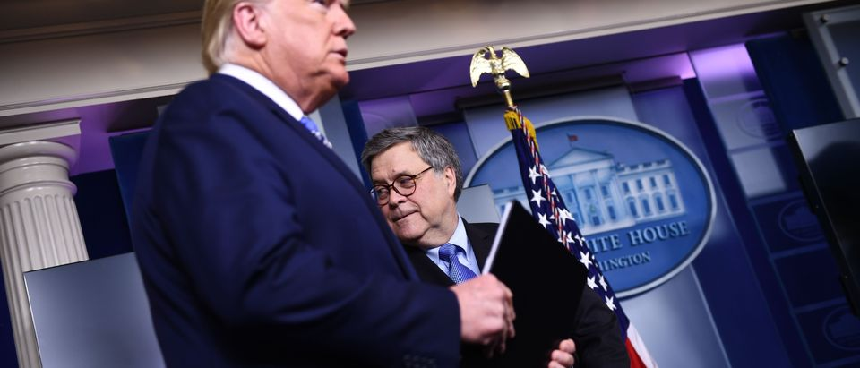 US President Donald Trump arrives as Attorney General William Barr looks on during the daily briefing on the novel coronavirus, COVID-19, at the White House on March 23, 2020, in Washington, DC. (Photo by BRENDAN SMIALOWSKI/AFP via Getty Images)