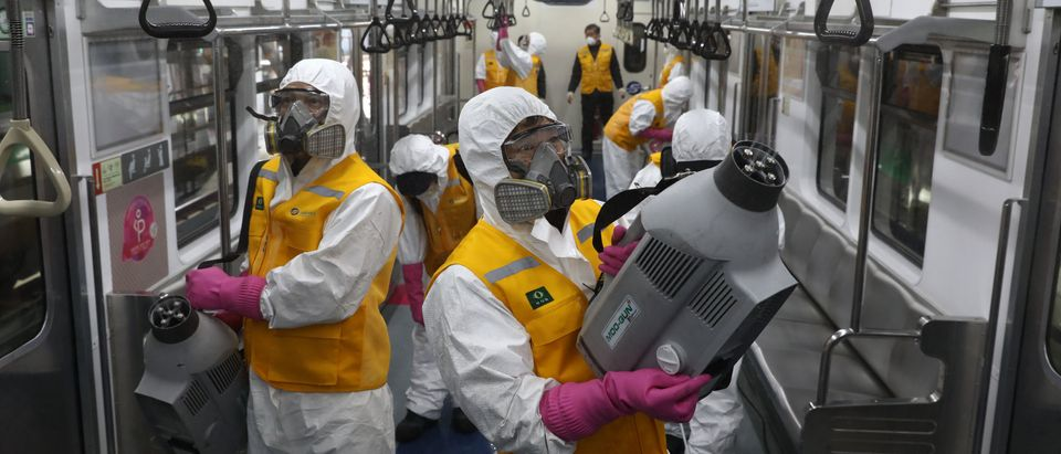 Disinfection workers wearing protective gear spray anti-septic solution against the coronavirus (COVID-19) in an subway at Seoul metro railway base on March 11, 2020 in Seoul, South Korea. (Chung Sung-Jun/Getty Images)