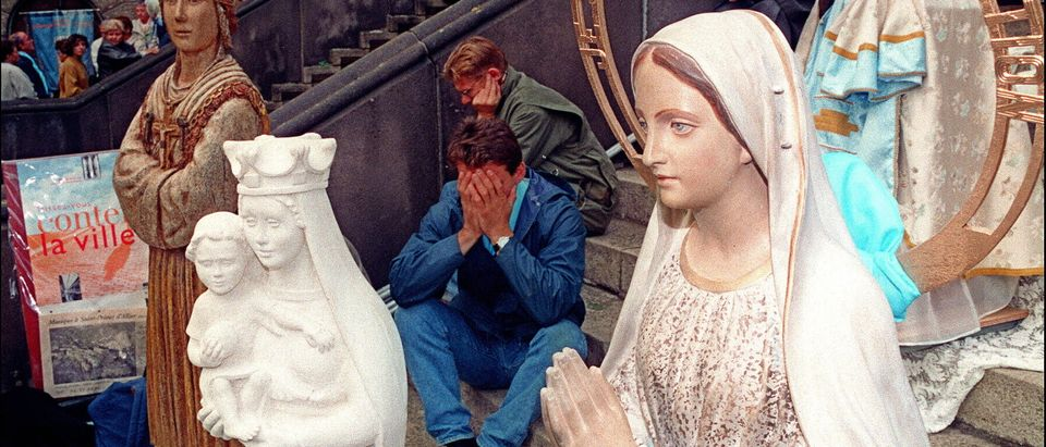 Catholic faithful pray among statues of the Virgin