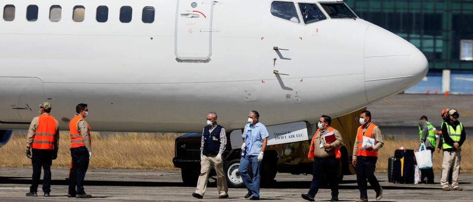 Government officials, wearing protective masks, stand next to a plane carrying migrants deported from the U.S. at La Aurora International airport, in Guatemala City