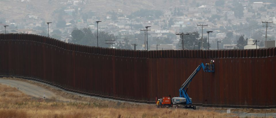 Workers weld sections of a newly replaced border wall with Tijuana, Mexico near the the Otay Mesa border crossing in San Diego, California