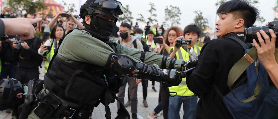 A riot policeman hits a man holding a camera as Hong Kong protesters rally in support of Xinjiang Uighurs' human rights in Hong Kong