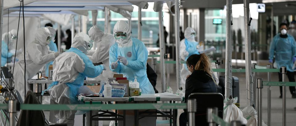 Medical staff wearing protective clothing take test samples for the COVID-19 coronavirus from a foreign passenger at a virus testing booth outside Incheon international airport, west of Seoul, on April 1, 2020. (JUNG YEON-JE/AFP via Getty Images)