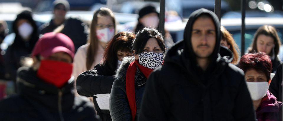 People wearing face masks in attempt to prevent the spread of coronavirus disease (COVID-19) wait outside a labour office in Sofia