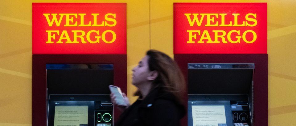 A woman walks past Wells Fargo bank in New York City