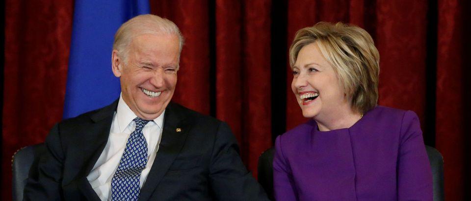 U.S. Vice President Joe Biden (L) and former Secretary of State Hillary Clinton (R) attend a ceremony to unveil a portrait honoring retiring Senate Minority Leader Harry Reid (D-NV). REUTERS/Jonathan Ernst