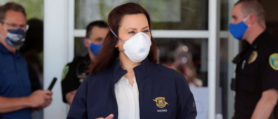 Michigan Governor Gretchen Whitmer wears a face mask as she arrives to address the media about the flooding along the Tittabawassee River, after several dams breached, in downtown Midland