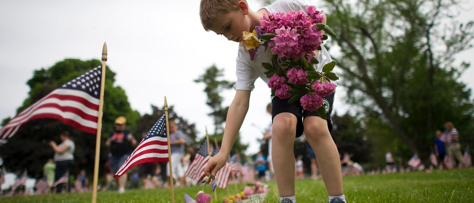 Alex Teeter places flowers on the grave sites of Battle of Gettysburg soldiers during a ceremony at National Soldier's Cemetery following the Gettysburg Memorial Day parade in Gettysburg, Pennsylvania, May 26, 2014. parade in Gettysburg, Pennsylvania,