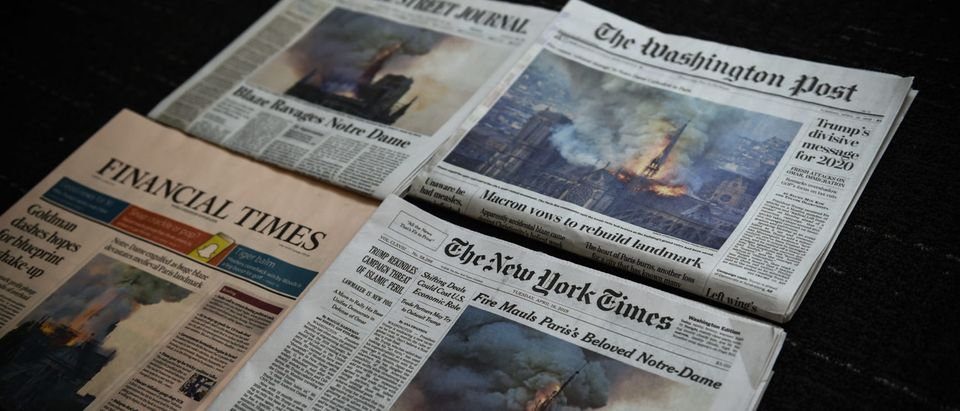 The US Newspapers editions of the New York Times, The Washington Post, The Wall Street Journal and the Financial Times display images of Notre-Dame Cathedral burning in Paris on their front page on April 16, 2019 in Washington DC. (ERIC BARADAT/AFP via Getty Images)