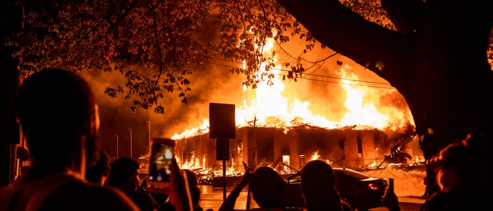 People look on as a construction site burns in a large fire near the Third Police Precinct on May 27, 2020 in Minneapolis, Minnesota. (Stephen Maturen/Getty Images)