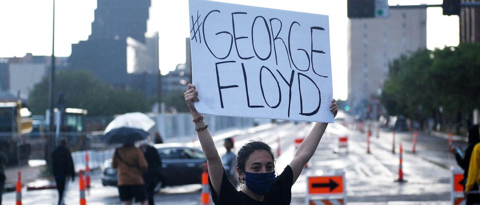 A woman holds a sign as protestors gather outside the St. Louis Police Department Headquarters on May 28, 2020 in St Louis, Missouri. (Michael B. Thomas/Getty Images)