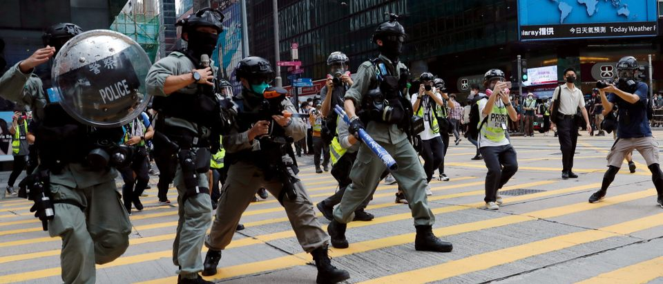 Riot police disperse anti-government demonstrators during a lunch time protest in Central, as a second reading of a controversial national anthem law takes place in Hong Kong