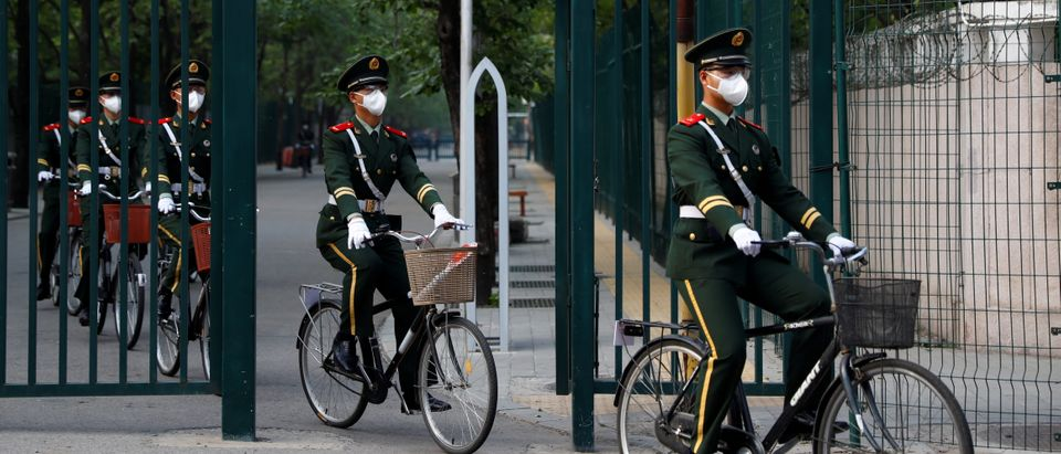 Chinese paramilitary police officers wear protective masks as they ride bicycles, while the spread of the coronavirus disease (COVID-19) continues in Beijing, China April 29, 2020. REUTERS/Thomas Peter
