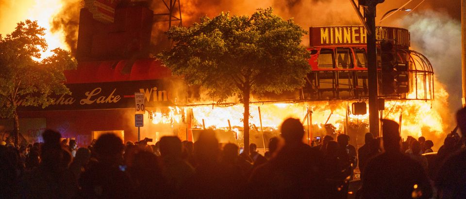 TOPSHOT - Protesters gather in front of a liquor store in flames near the Third Police Precinct on May 28, 2020 in Minneapolis, Minnesota, during a protest over the death of George Floyd, an unarmed black man, who died after a police officer kneeled on his neck for several minutes. - A police precinct in Minnesota went up in flames late on May 28 in a third day of demonstrations as the so-called Twin Cities of Minneapolis and St. Paul seethed over the shocking police killing of a handcuffed black man. The precinct, which police had abandoned, burned after a group of protesters pushed through barriers around the building, breaking windows and chanting slogans. A much larger crowd demonstrated as the building went up in flames. (Photo by kerem yucel / AFP) (Photo by KEREM YUCEL/AFP via Getty Images)