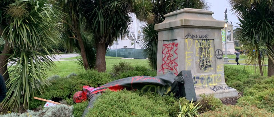St Junipero Serra statue faces the ground memorial after being vandalised with red spray painting in San Francisco