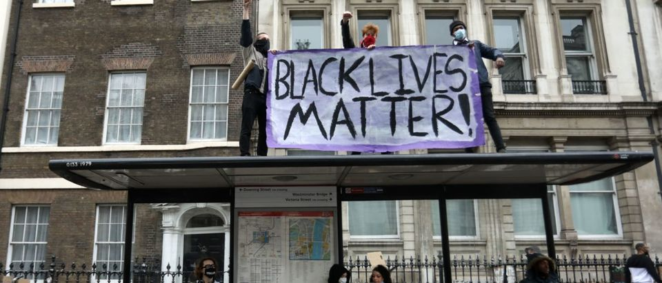 Protesters display a banner as they stand on a bus stop in central London after attending a demonstration outside the US Embassy, on June 7, 2020, organised to show solidarity with the Black Lives Matter movement in the wake of the killing of George Floyd, an unarmed black man who died after a police officer knelt on his neck in Minneapolis. - Taking a knee, banging drums and ignoring social distancing measures, outraged protesters from Sydney to London on Saturday kicked off a weekend of global rallies against racism and police brutality. (Photo by ISABEL INFANTES / AFP) (Photo by ISABEL INFANTES/AFP via Getty Images)