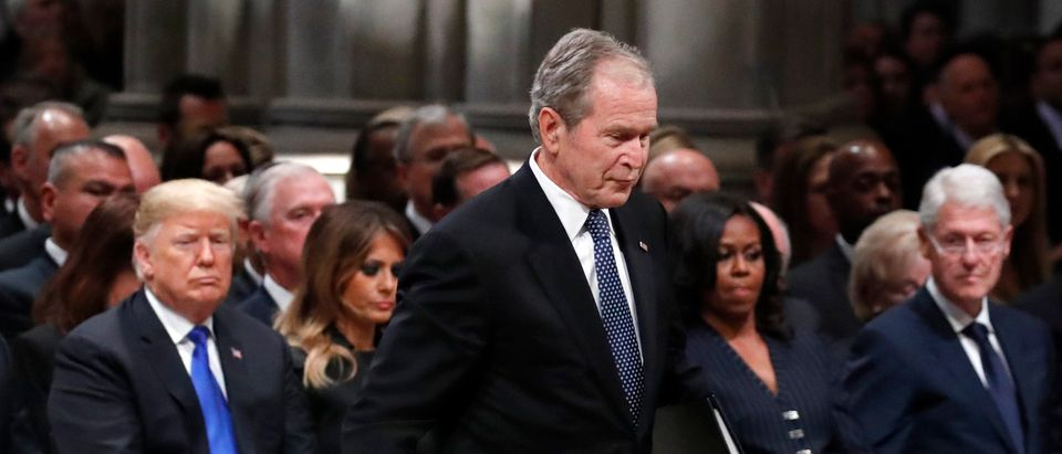 (AFP OUT) Former President George W. Bush walks past President Donald Trump, first lady Melania Trump, former first lady Michelle Obama and former President Bill Clinton to give a eulogy for his father, former President George H.W. Bush during the State Funeral at the Washington National Cathedral on December 5, 2018 in Washington, DC. (Alex Brandon - Pool/Getty Images)