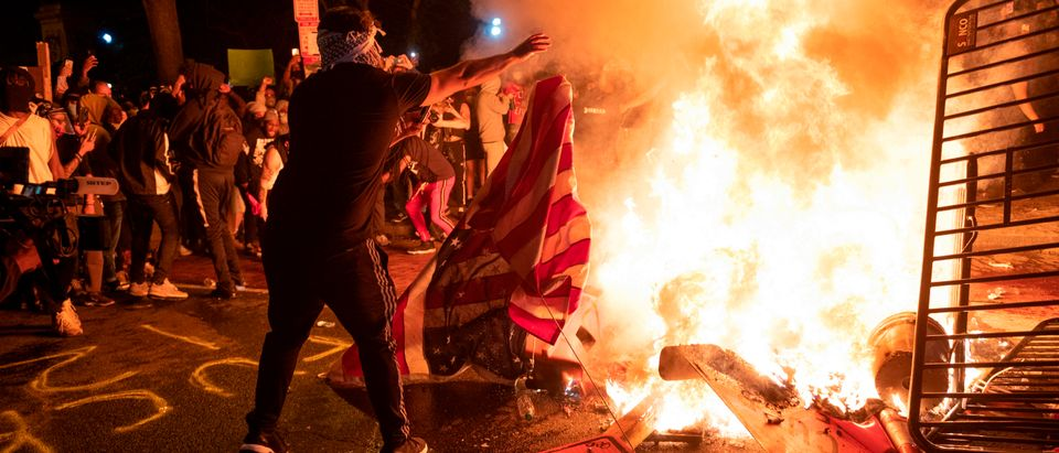 A protester throws a US flag into a burning barricade during a demonstration against the death of George Floyd near the White House on May 31, 2020 in Washington, DC. - Thousands of National Guard troops patrolled major US cities after five consecutive nights of protests over racism and police brutality that boiled over into arson and looting, sending shock waves through the country. The death Monday of an unarmed black man, George Floyd, at the hands of police in Minneapolis ignited this latest wave of outrage in the US over law enforcement's repeated use of lethal force against African Americans -- this one like others before captured on cellphone video. (Photo by ROBERTO SCHMIDT/AFP via Getty Images)