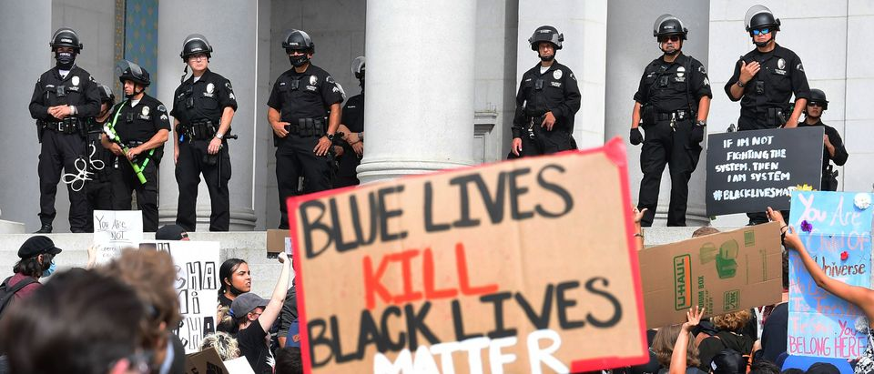 Protesters hold placards during a march over the death of George Floyd, an unarmed black man, who died after a police officer kneeled on his neck for several minutes, in front of the Los Angeles City Hall on June 1, 2020 in Los Angeles, California. - The city and county of Los Angeles has extended curfew for a third night following a weekend of looting in southern California by people taking advantage of those protesting the death of George Floyd. (Photo by FREDERIC J. BROWN/AFP via Getty Images)