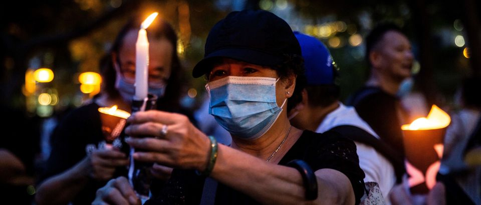 Activists light candles during a remembrance gathering outside Victoria Park in Hong Kong on June 4, 2020, after an annual vigil that traditionally takes place in the park to mark the 1989 Tiananmen Square crackdown was banned on public health grounds because of the COVID-19 coronavirus pandemic. (Photo: Isaac Lawrence/AFP via Getty Images)