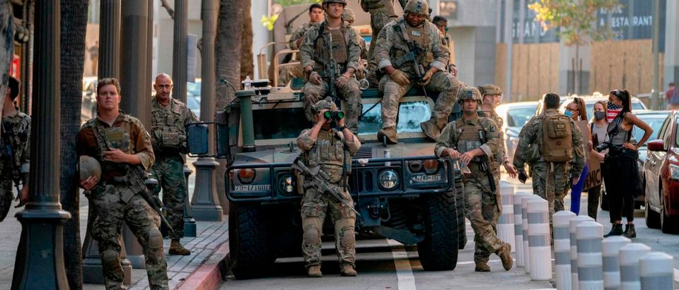 Members of the California National Guard speak to and watch protesters during a demonstration over the death of George Floyd while in Minneapolis Police custody, in downtown Los Angeles, California, June 6, 2020. - Demonstrations are being held across the US following the death of George Floyd on May 25, 2020, while being arrested in Minneapolis, Minnesota. (Photo by Kyle Grillot / AFP / Getty Images)