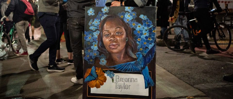 A demonstrator holds a painting of Breonna Taylor during a protest near the Seattle Police Departments East Precinct on June 7, 2020 in Seattle, Washington. (David Ryder/Getty Images)