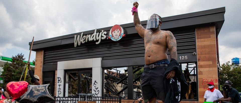 ATLANTA, GA - JUNE 14: A man gestures at the site of a Wendy's restaurant set ablaze overnight on June 14, 2020 in Atlanta, Georgia. Rayshard Brooks, 27, was shot and killed on June 12th by police in a struggle following a field sobriety test at the Wendy's. (Photo by Dustin Chambers/Getty Images)