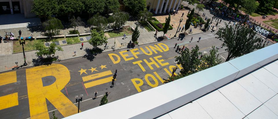 """WASHINGTON, DC - JUNE 08: People walk down 16th street after """"Defund The Police"""" was painted on the street near the White House on June 08, 2020 in Washington, DC. After days of protests in DC over the death of George Floyd, DC Mayor Muriel Bowser has renamed that section of 16th street """"Black Lives Matter Plaza"""". (Photo by Tasos Katopodis/Getty Images)"""