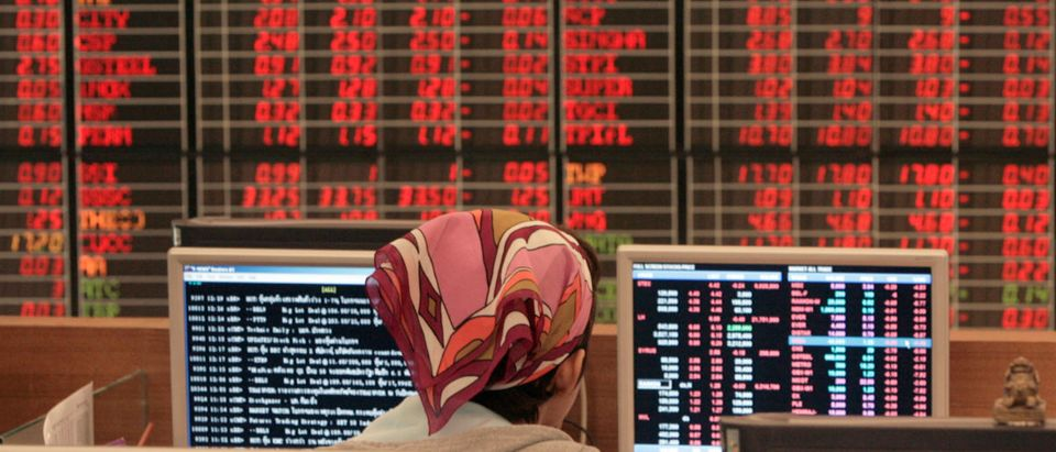 A Thai investor watches live market data on a monitor at a stock brokers' office in central Bangkok