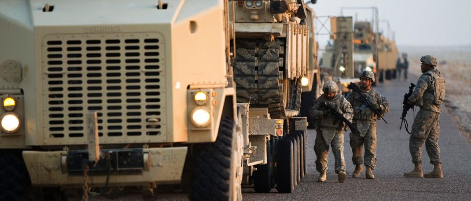 Soldiers perform a security check on their MRAP vehicles near the Kuwaiti border as part of the last U.S. military convoy to leave Iraq