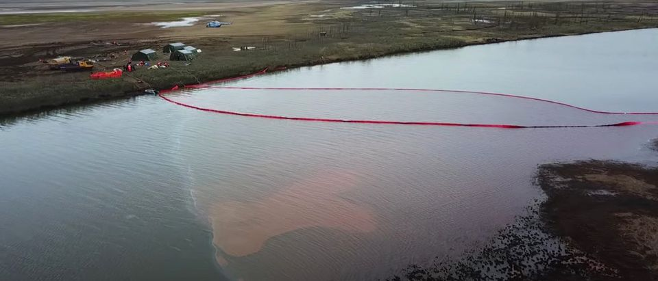 Rescuers work at the site of a huge leak of fuel into the river after an accident at a power plant outside Norilsk