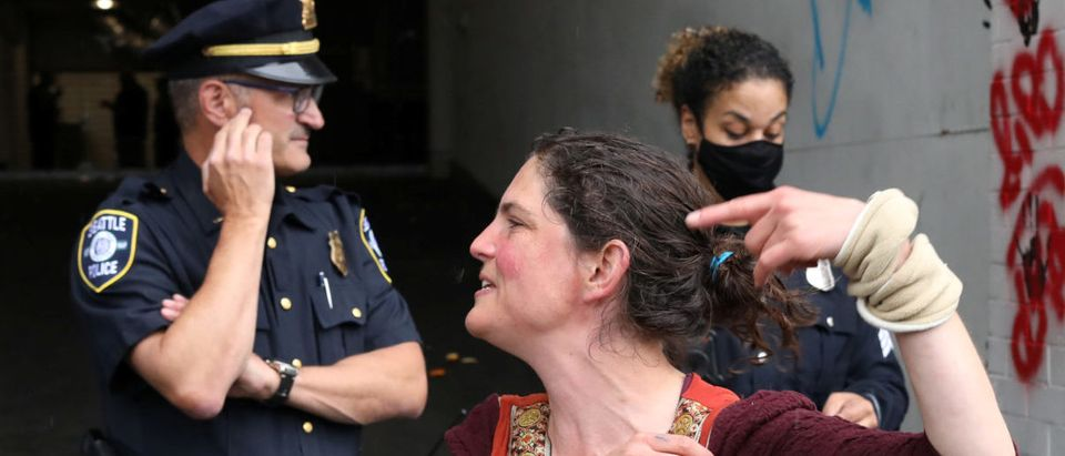 A woman gestures in front of police officers at the entrance of Seattle Police Department East Precinct in Seattle