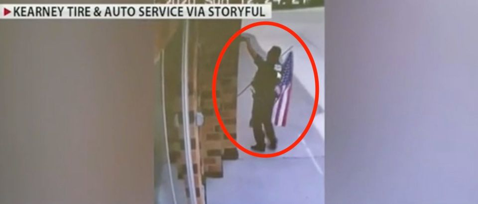 Police officer Jeff Schwarz rescues a fallen flag at Kearney Tire and Auto. Screenshot/Fox News