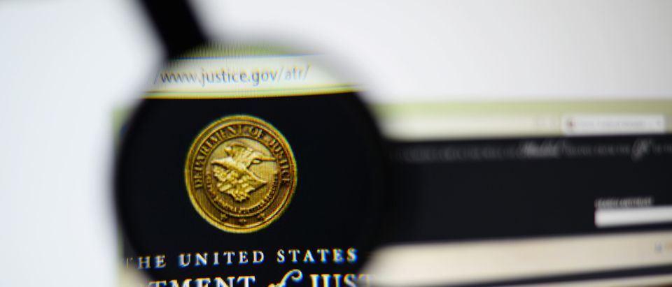 LISBON, PORTUGAL - December 9, 2014: Photo of the United States Department of Justice (DOJ) homepage on a monitor screen through a magnifying glass. (SHUTTERSTOCK/Gil C)