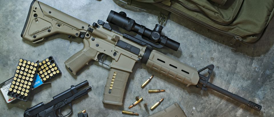 AR-15 with khaki furniture, 5.56x45mm ammunition, and a semi-automatic handgun/Shutterstock