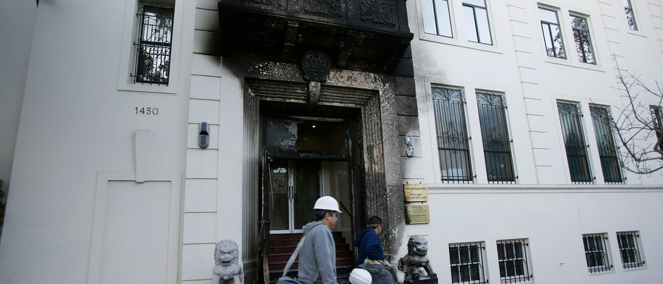 Construction workers walk past the damaged front of the Chinese consulate in San Francisco