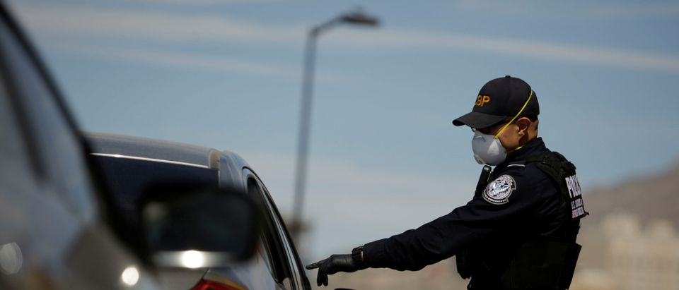 U.S. Customs and Border Protection police officer talks to a driver as the coronavirus disease (COVID-19) outbreak continues at Paso del Norte International Border bridge as taken from Ciudad Juarez,