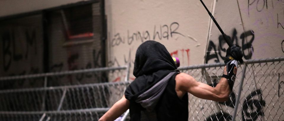 A demonstrator hits pieces of fencing blocking a door used by federal law enforcement officers deployed under the Trump administration's executive order to protect federal monuments and buildings, during a protest against racial inequality in Portland, Oregon, U.S., July 19, 2020. (REUTERS/Caitlin Ochs)