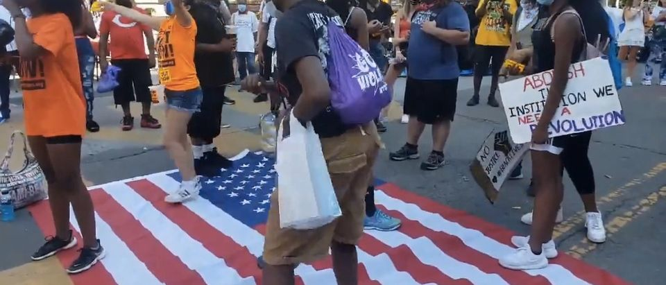 BLM protesters dance on the American flag. Screenshot/Twitter