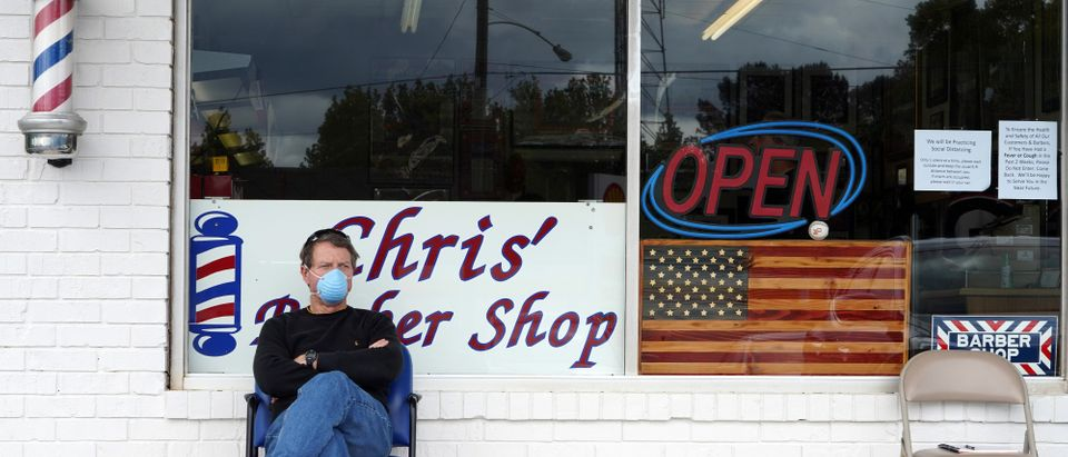 Dan Settle sits outside Chris' Barber Shop as he waits his turn for a haircut in Lilburn, Georgia on April 24, 2020. - Georgia Governor Brian Kemp eased restrictions allowing some businesses such as barber shops to reopen to get Georgia's economy going during the coronavirus pandemic. (Photo by Tami Chappell/AFP via Getty Images)
