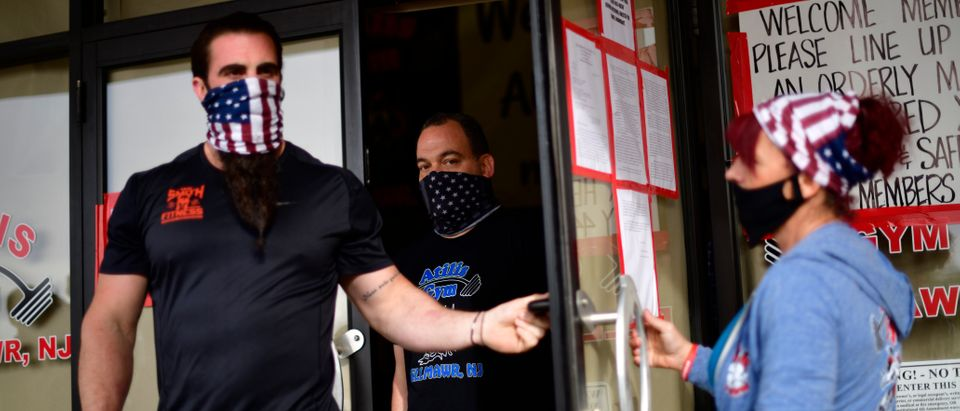 BELLMAWR, NJ - MAY 20: Employees exit to greet patrons lining up outside the Atilis Gym on May 20, 2020 in Bellmawr, New Jersey. The gym has opened for the third consecutive day, defying the New Jersey Governor's mandate that many retail businesses stay closed due to the coronavirus pandemic. (Mark Makela/Getty Images)