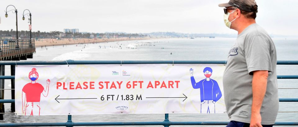 A man wearing his facemask walks past a banner reminding people of social distancing guidelines on Santa Monica Pier which re-opened on June 25 after closure for over three months due to the coronavirus pandemic, on June 26, 2020 in Santa Monica, California. - A gradual re-opening of businesses continues across the state, despite a continued rise in coronavirus cases. (Photo by FREDERIC J. BROWN/AFP via Getty Images)