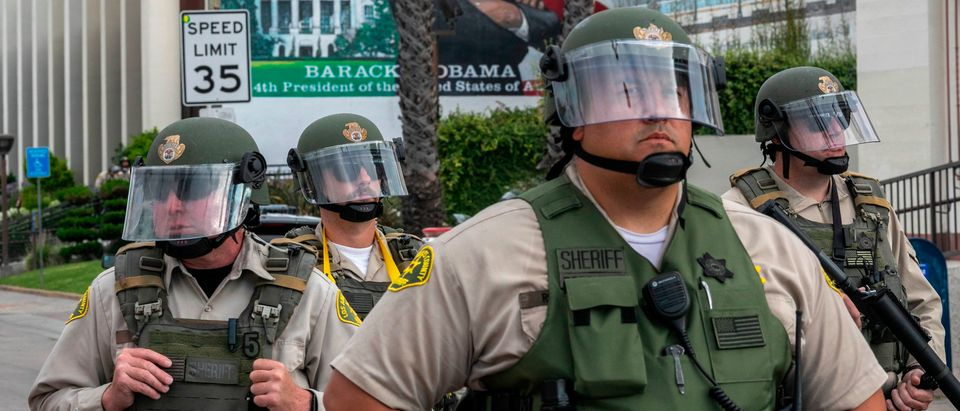 Sheriff's deputies stand guard near a mural of President Barack Obama as activists and relatives of Andres Guardado, who was shot and killed by a sheriff's deputy in Gardena, rally to call on the city to rescind its policing contract, near the Compton Sheriff's Station in Compton, California, on June 28, 2020. (Photo by DAVID MCNEW/AFP via Getty Images)