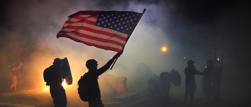 PORTLAND, OR - JULY 21: A protester flies an American flag while walking through tear gas fired by federal officers during a protest in front of the Mark O. Hatfield U.S. Courthouse on July 21, 2020 in Portland, Oregon. The federal police response to the ongoing protests against racial inequality has been criticized by city and state elected officials. (Photo by Nathan Howard/Getty Images)