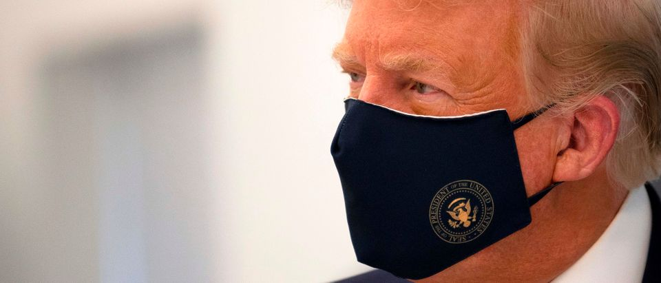 US President Donald Trump wears a mask as he tours a lab where they are making components for a potential vaccine at the Bioprocess Innovation Center at Fujifilm Diosynth Biotechnologies in Morrisville, North Carolina on July 27, 2020. (Photo by JIM WATSON/AFP via Getty Images)