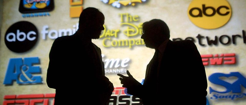PASADENA, CA - JULY 23: Michael Eisner (L), chairman and CEO of the Walt Disney Company, talks with Mel Woods (R), president and CEO of the Haim Saban, in front of a projection, showing logos of the new acquisitions, during announcement of 100 percent purchase of Fox Family Worldwide and Haim Saban July 23, 2001 in Pasadena, CA. Fox Family and its subsidiaries will be renamed ABC Family. (FREDERICK M. BROWN/AFP via Getty Images)