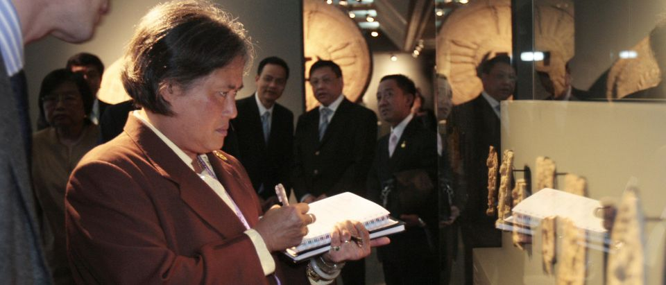 """Princess Maha Chakri Sirindhorn (L) from Thailand, daughter of Thai King Bhumibol Adulayadej, takes notes as she visits, in Paris on March 19, 2009, the exhibition """"Dvaravatî to the sources of Buddhism in Thailand"""" (Dvaravati, aux Sources du Bouddhisme en Thaïlande), which takes place at Asian Arts-Guimet Museum, until May 25th, 2009. 145 pieces of work part of the collections of twelve of the principal Thai national museums, completed by 19 pieces belonging to the Guimet Museum, illustrate the richness and precision of the iconography of the Dvaravati """"kingdom"""". (Photo by Francois Guillot/AFP via Getty Images)"""