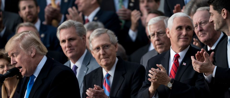 """House Majority Leader Representative Kevin McCarthy (R-CA) (2L), Senate Majority Leader Senator Mitch McConnell (R-KY) (C), US Vice President Mike Pence (2R), Speaker of the House Paul Ryan (R-WI) (R) and others listen while US President Donald Trump speaks about newly passed tax reform legislation during an event December 20, 2017 in Washington, DC. Trump hailed a """"historic"""" victory Wednesday as the US Congress passed a massive Republican tax cut plan, handing the president his first major legislative achievement since taking office nearly a year ago. (BRENDAN SMIALOWSKI/AFP via Getty Images)"""