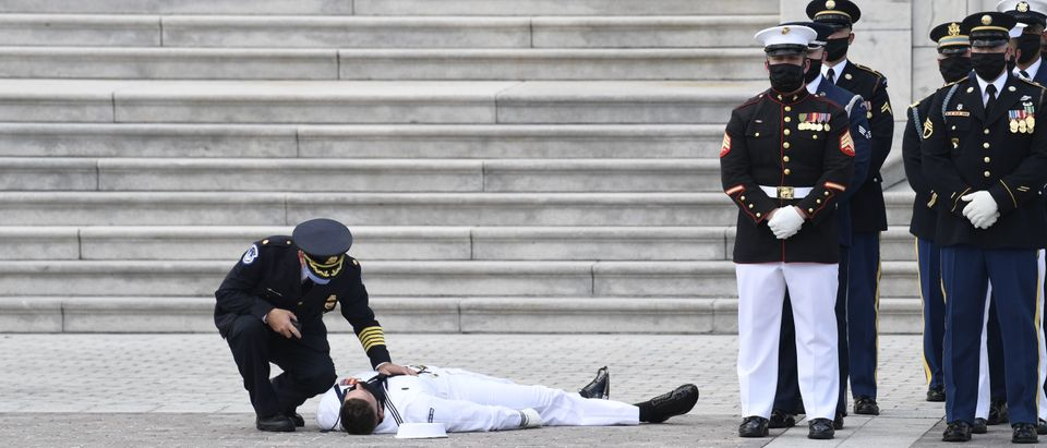A member of a US military honor guard is checked on after collapsing in the heat of the day awaiting the casket of civil rights pioneer and longtime US Representative John Lewis (D-GA), who died July 17. SUSAN WALSH/POOL/AFP via Getty Images